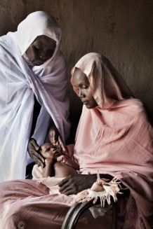 Midwife Rabha Abdalraheem Ahmed, 56 years old, visiting Raheeba Mohammed, 25 years old, and her forth newborn girl Madeena, 25 days old. Marin village, Rahad locality, Gedaref State. Sudan, 2015.