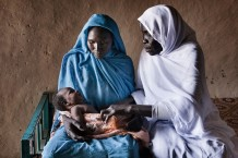 Maryam Mohammed, 24 years old, with her sixth newborn boy Abdalhaleem, 23 days old, and midwife Rabha Abdalraheem Ahmed, 56 years old, at Marin, Rahad. Gedaref State, Sudan, 2015.