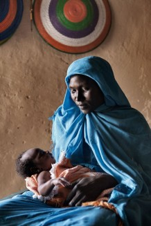 Maryam Mohammed, 24 years old, with her sixth newborn boy Abdalhaleem, 23 days old, delivered at home with the assistance of trained midwife Rabha Abdalraheem Ahmed. Marin village, Rahad locality, Gedaref Sate. Sudan 2015