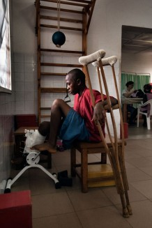 Surgical and Paediatric Centre, physiotherapy room. Mohammed, 15 years old, another victim of car accidents. In the background treatment for infants with Erb's palsy. Goderich, Freetown, Sierra Leone 2017