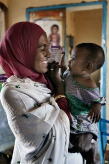 Amany Dowd, cleaner of the health center, taking drugs for her daughter Dalia Aboadem, 1 year old, sick with flue, by medical assistant Ahmed Hassan Ahmed. Drugs are provided by Italian Cooperation. Ardalhager health centre, Girba locality, Kassala State. Sudan 2015