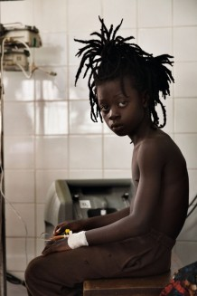 Paediatric Centre, where 150 children are visited every day, emergency room. Michael, 9 years old, is lethargic and can't keep food down. His mother died one year ago. Goderich, Freetown, Sierra Leone 2017