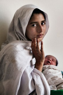 Nazi, 10 years old, with her newborn sister. Nowshera District, KPK, Pakistan, 2014.