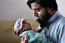 Shabir Kamal, 37 years old, property and land dealer, Fatima's husband, posing for the Every Newborn Action Plan with his newborn girl, 15 days old, at his mother in law's house. After delivering, according to tradition, Pakistani women stay at their mothers' houses for 40 days. Taxila, Punjab. Pakistan 2014
